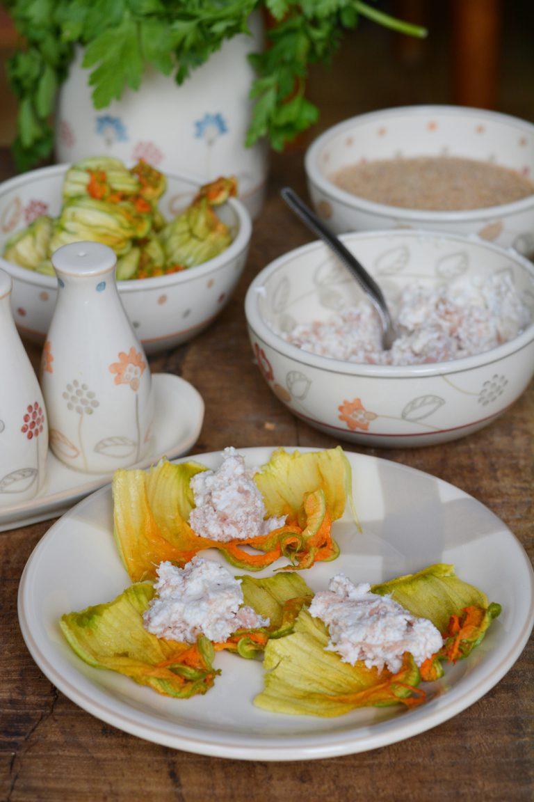 Lavare accuratamente i fiori di zucca e sistemateli aperti in un piatto e farciteli con il ripieno