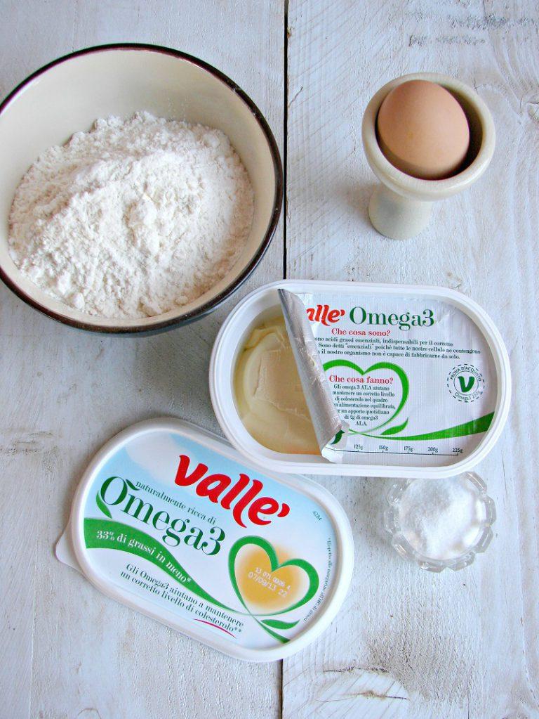 Impastate la farina con la margarina, l'uovo e il sale. Realizzate un impasto compatto, avvolgetelo nella pellicola e ponetelo in frigo per un'ora.