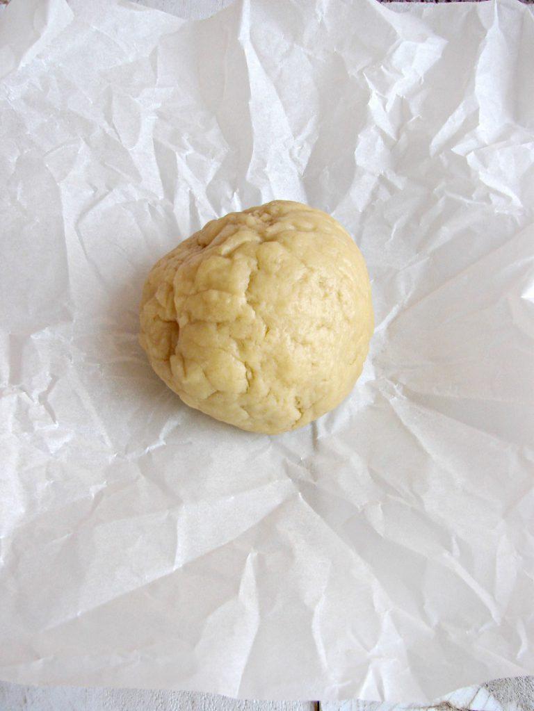Trascorso questo tempo, manipolate l'impasto leggermente e poi stendetelo con un matterello su un piano leggermente infarinato ad uno spessore di circa 2 mm. Coppate con un coppa pasta da 10 cm di diametro, disponete i cerchi dentro una teglia per muffin; con i rebbi di una forchetta bucherellate il fondo, rivestite con dei rettangoli di carta forno, riempite con dei fagioli secchi e infornate in forno caldo a 160°C per dieci minuti, tirate fuori la teglia dal forno, eliminate i fagioli e cuocete ancora dieci minuti o fino a doratura. Tirate fuori la teglia, fate intiepidire e poi sformate le tartellette facendole raffreddare completamente.