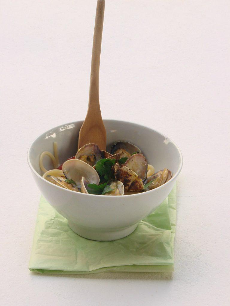 Scaldate l'olio in una padella capiente con l'aglio rimasto schiacciato, il peperoncino tagliato a fettine, la scorza di limone e il succo; versate le vongole e fate insaporire pochi minuti. Lessate la pasta in abbondante acqua salata, scolatela al dente direttamente nella padella, cuocete ancora pochi istanti, mescolando. Spegnete il fuoco cospargete con il prezzemolo tritato e servite subito.