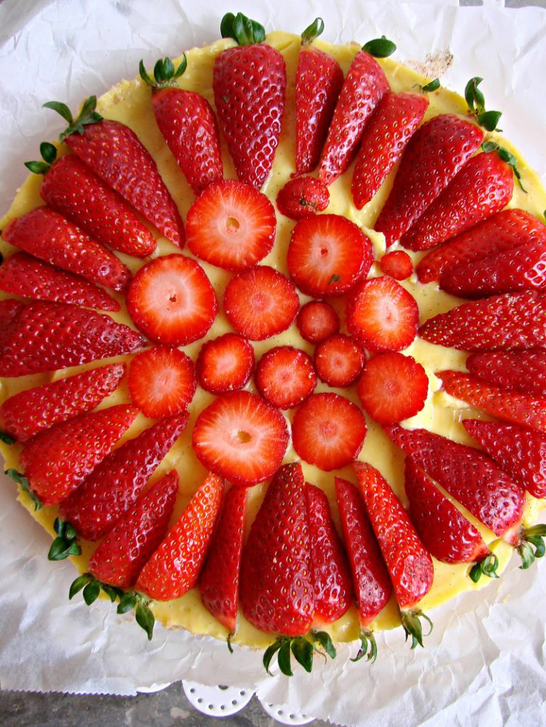 Prima di servire affettate le fragole e decorate la superficie della torta.