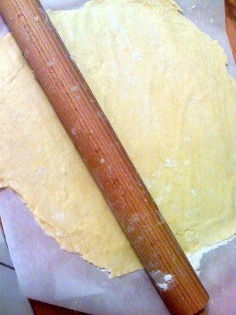 Trascorso questo tempo, stendete direttamente su carta forno infarinando bene la carta e il mattarello. Adagiate la carta con la pasta su una tortiera bassa per crostata, aggiustate i bordi  e bucherellate il fondo con una forchetta. Mettete la tortiera in freezer per 15-20 minuti; intanto, accendete il forno a 200 gradi