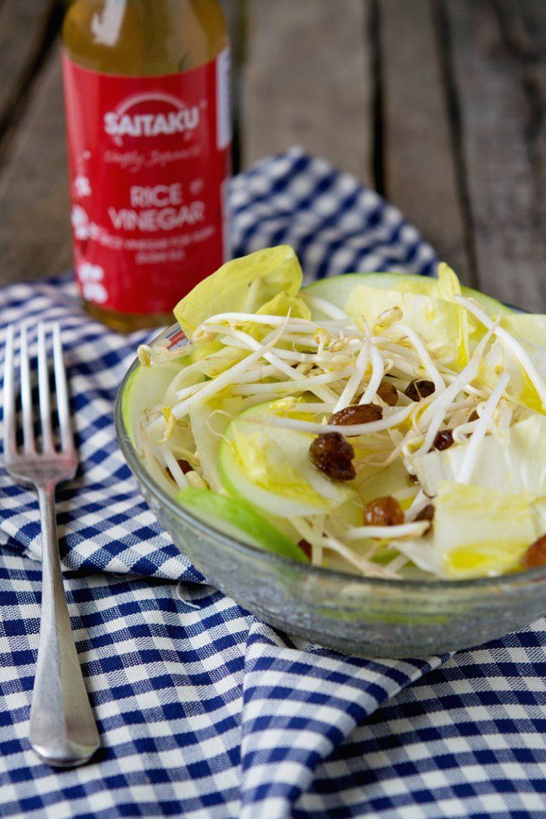 In una ciotola unire le fettine di mela, l'indivia, l'uvetta strizzata e i germogli di soia. Condire, solo al momento di portare in tavola, con l'emulsione di olio e aceto, mescolare e servire.