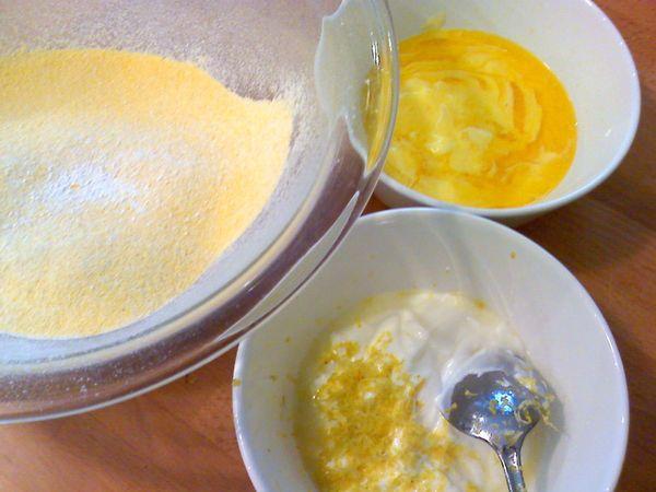 Accendete il forno a 180 gradi. Fate sciogliere la margarina e mettete da parte. Mescolate le due farine e il lievito e setacciate; mescolate a parte lo yogurt con la scorza e il succo di limone