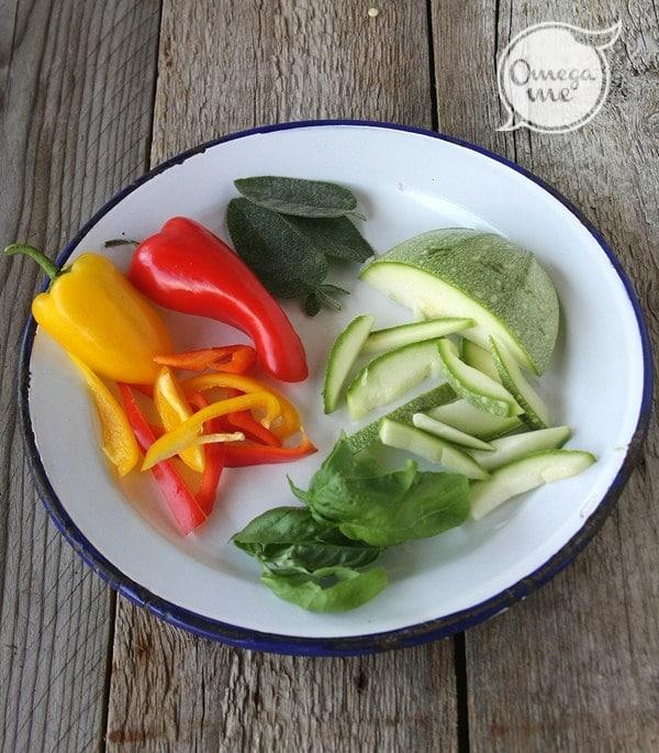 Affettate sottilmente i peperoni e le zucchine.