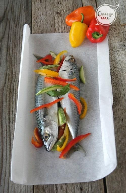 Prendete 4 fogli di carta da forno, adagiate due sgombri per ogni foglio. Distribuite le verdurine sui pesci, mettete alcune foglie di basilico con sale e pepe ed un filo di olio extravergine d'oliva prima di chiudere il cartoccio a pacchetto.