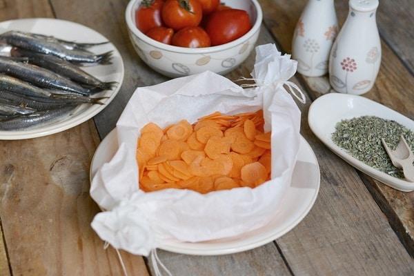 in un cartoccio di carta forno, sistemare le carote tagliate a rondelle