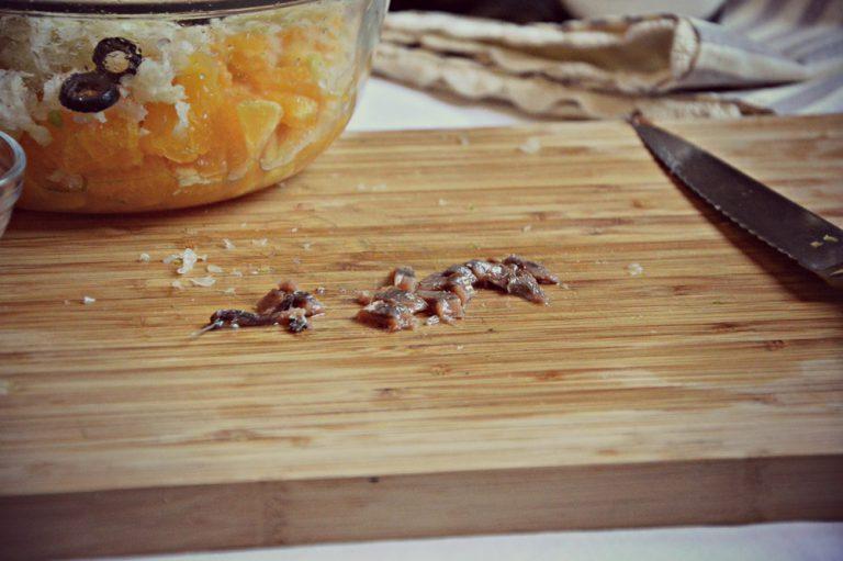 Tagliate a rondelle le olive, spezzettate l'acciuga e aggiungetele al composto di frutta