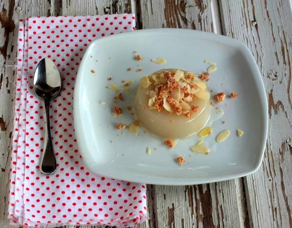 Sformate i budini in un piattino e serviteli con l'amaretto sbriciolato e le mandorle in scaglie.