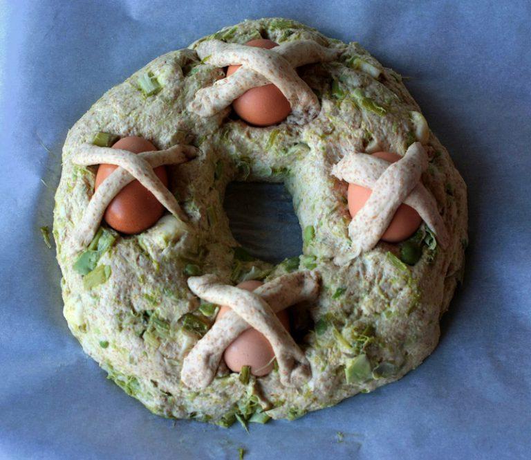 Trascorsa l'ora, in un piano infarinato prendete la pasta, toglietene una piccola parte, e lavorandola iniziate ad inglobare gli ingredienti ed il parmigiano grattugiato, dategli la forma allungata e quindi a ciambella, mettetelo su di una teglia coperta da carta forno. Create quattro fossette dove inserirete le uova lavate ed asciugate. Con la pasta tenuta da parte fate otto strisce e create delle croci sopra il guscio. Mettere in forno a 160-180 per circa 1 ora.