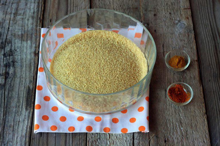 In un pentolino portate a bollore l'acqua con mezzo cucchiaino di sale – mettete il cous cous precotto in una ciotola con i 3 cucchiai di olio extravergine d'oliva, il curry e la curcuma, versate l'acqua e copritelo con un coperchio lasciandolo riposare per 5 minuti. Trascorso il tempo sgranate con cura il cous cous con una forchetta e tenetelo da parte.