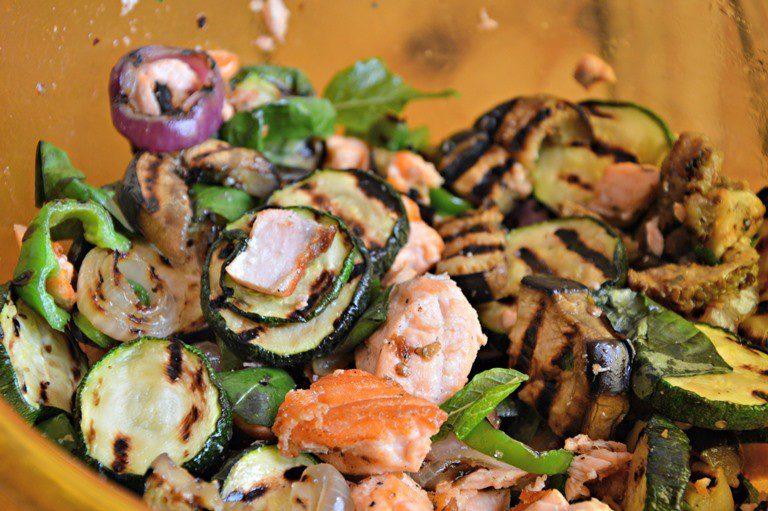 Ponete la verdura arrostita dentro un insalatiera, aggiungete i pomodorini tagliati a meta, e il salmone, salate, pepate e condite con l'olio.
