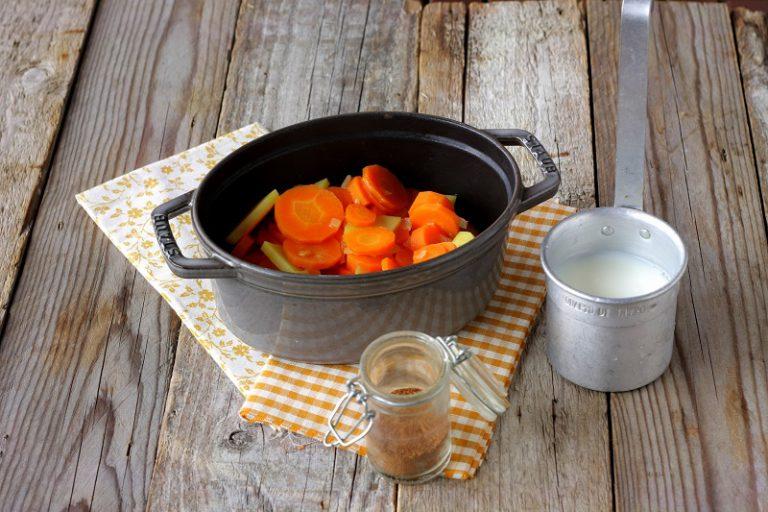 Aggiungete il latte scremato, il brodo vegetale e le spezie e proseguite la cottura per altri 20 minuti o fino a che le carote non risulteranno morbide.
