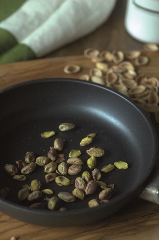 Tostare i pistacchi in una pentola anti aderente e ammollare per pochissimi minuti i mirtilli rossi nell'acqua tiepida con qualche seme di coriandolopestato. Negli ultimi minuti di cottura delle cipolleunire i pistacchi e i mirtilli sgocciolati. Regolare disale e mettere da parte a riposare.