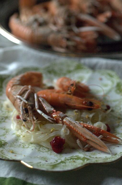 Servire i crostacei sopra una cucchiaiata di saor utilizzando un piatto liscio e decorando con una macinata di pepe nero.