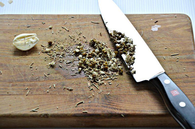 Schiacciate con la lama del coltello il pepe verde sgocciolato. Tritatelo con l'aglio e il rosmarino.