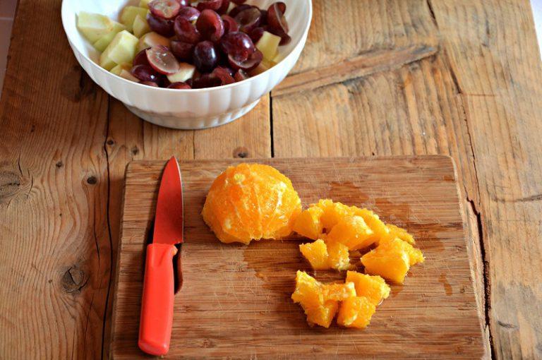 Tagliate a metà gli acini d'uva ed eliminate i noccioli. Pelate a vivo l'arancia e tagliatela a pezzetti. Riunite la frutta tutta insieme dentro la ciotola e mescolate.