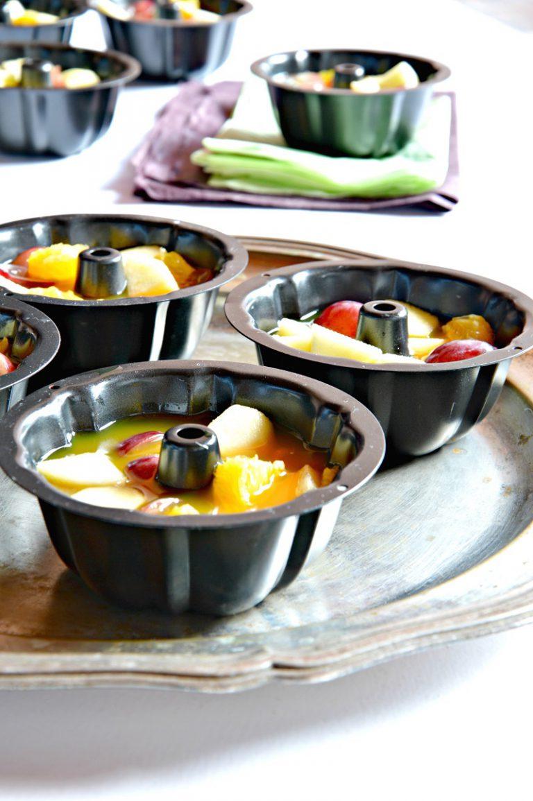 Distribuite qualche fogliolina di menta sul fondo e la frutta dentro le ciotoline che avrete scelto per gli stampi. Suddividete la gelatina e ponete in frigo per due ore.