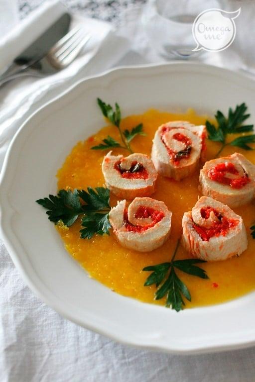 Versare nel piatto di portata la crema di peperoni gialla e posare i rotolini. Decorare con prezzemolo.