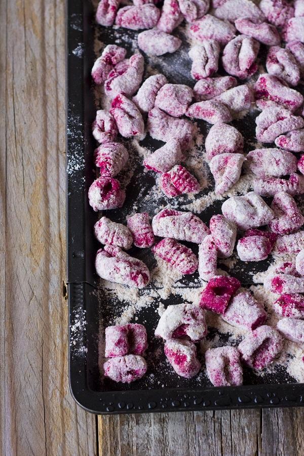 Frullate la barbabietola ed unitela alle patate con la farina integrale, due pizzichi di sale ed i tuorli d'uovo. Mescolate fino ad ottenere un impasto omogeneo. Fate dei cilindri regolari e formate dei gnocchi di 1-2 cm, rigateli con i rebbi di una forchetta o con l'apposito rigagnocchi.
