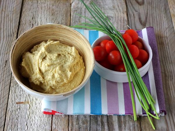 Tagliate il pane a fettine, spalmate con l'hummus, ricoprite con pomodorini freschi tagliati in quattro ed erba cipollina fresca e servite.