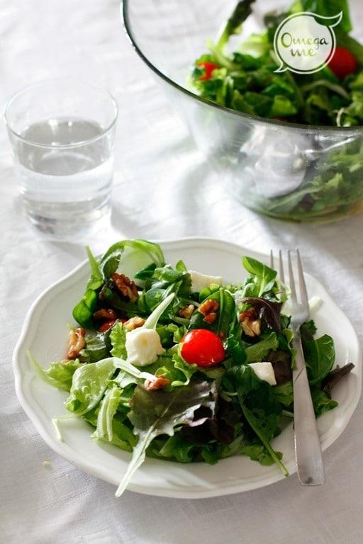 Lavare l'insalata e passarla alla centrifuga. Versarla in una ciotola e condire con pomodorini ciliegino tagliati a metà, cubetti di formaggio fresco e gherigli di noci spezzettati grossolanamente.