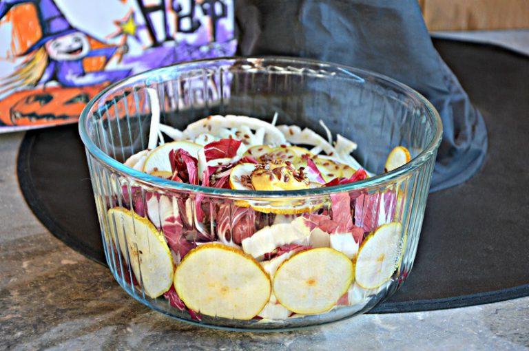 Riunite la frutta e la verdura dentro una ciotola trasparente,unite i semi di lino, condite con il sale, l'olio, la senape e una macinata di pepe.