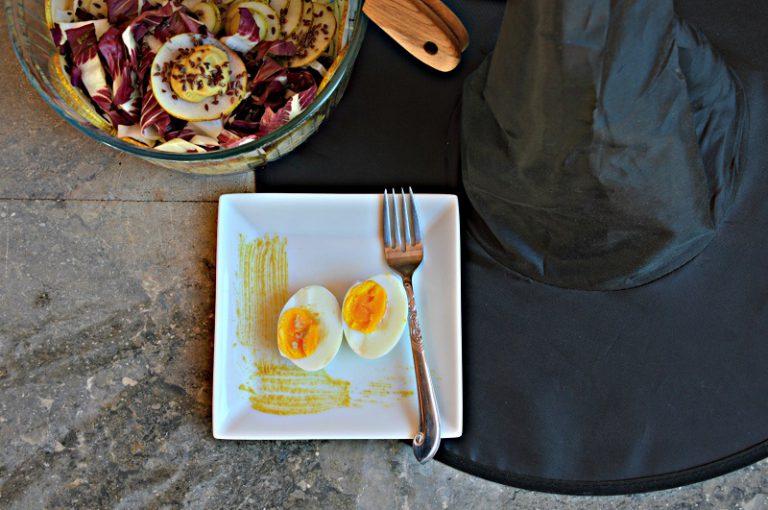 Servite l'insalata con le uova tagliate a metà.