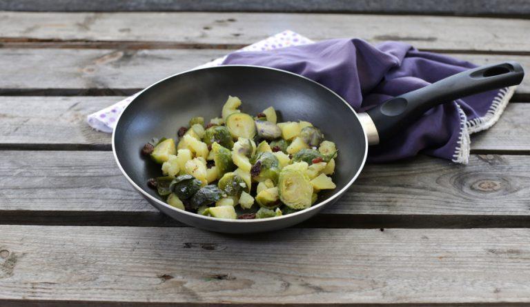 Sciogliete valle' in un tegame e saltate i cavoletti, le patate e l'uvetta strizzata ed un cucchiaio di semi di girasole.