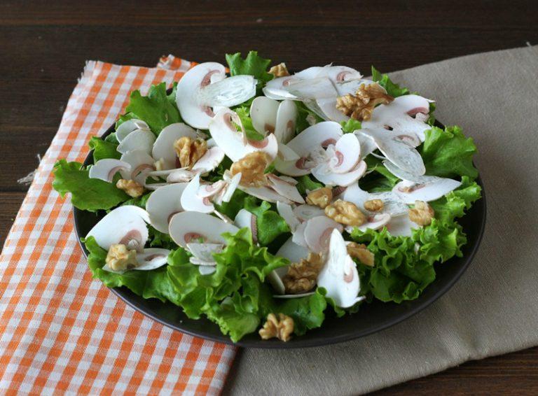 Appoggiate gli champignons sull'insalata, aggiungete le scaglie di parmigiano ed il prezzemolo, ed i gherigli di noce rotti grossolanamente.