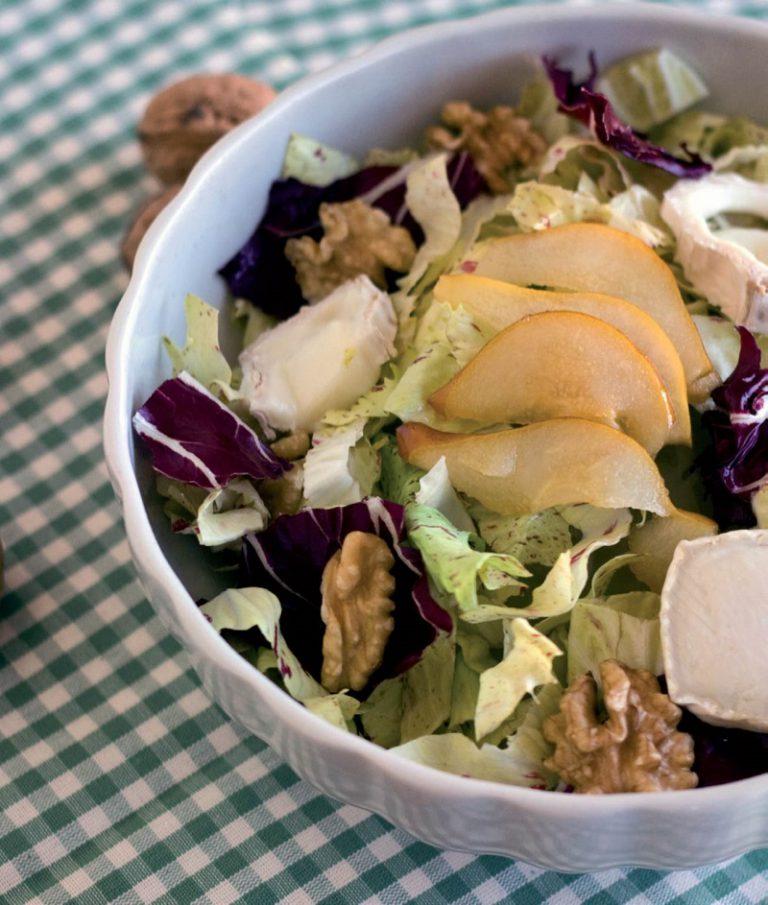 In ogni piatto preparare un fondo d'insalata, appoggiare le pere ancora tiepide, i gherigli di noce e una fettina di caprino.