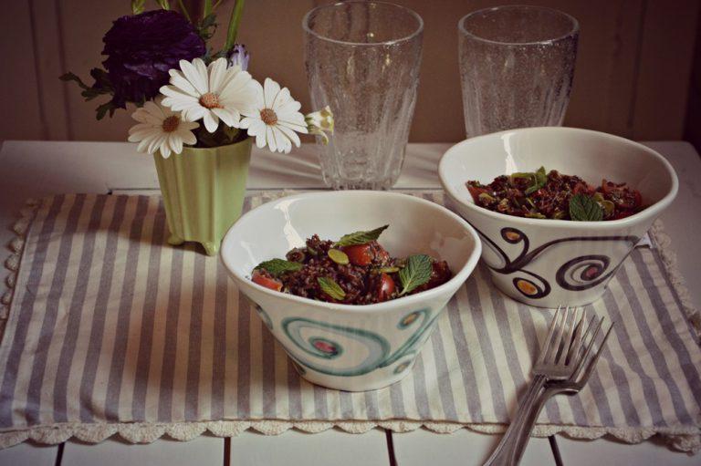 Cuocete il riso in acqua salata, scolatelo, ponetelo dentro una ciotola e conditelo con le fave, le olive tagliate a rondelle, i pomodorini tagliati a quarti e il pesto, mescolate, aggiustate di sale, decorate con le foglioline di menta e servite