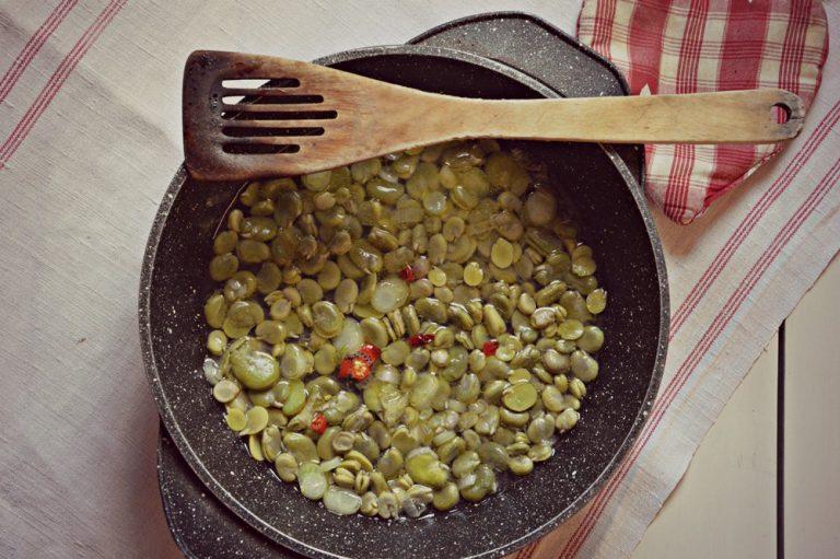 Affettate lo scalogno, ponetelo in un tegame con l'olio e un cucchiaio d'acqua, aggiungete il peperoncino e versate le fave, aggiungete mezzo bicchiere d'acqua e stufate portando a cottura.