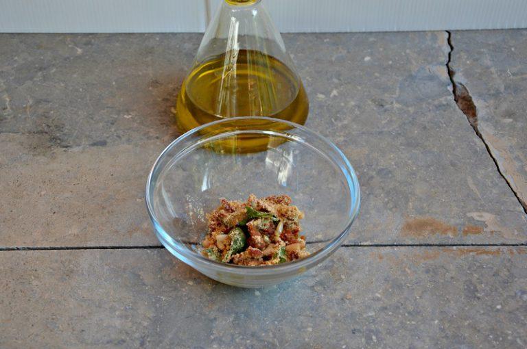 Mischiateli con qualche foglia di basilico spezzettata, il pan grattato, l'olio e i pinoli