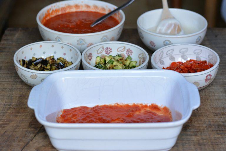 Passare in padella le verdure tagliate a dadini (non vanno fritte). In una terrina, ricoprite il fondo con qualche cucchiaio di salsa di pomodoro.