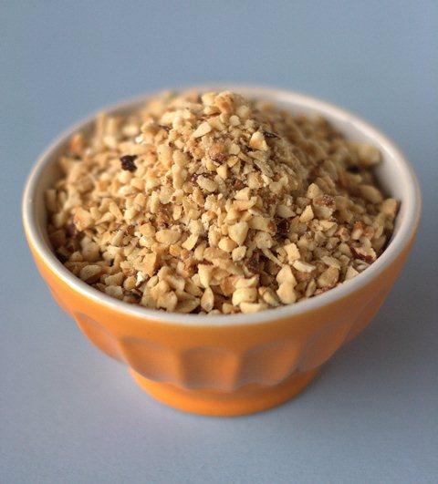 Nel mentre in un tegamino fate bollire lo zucchero con l'acqua per 6-7 minuti, togliete dal fuoco ed aggiungete la granella di nocciole, mescolate accuratamente un mestolo di legno.