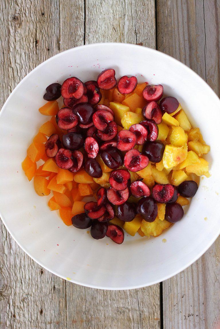 Lavate e tagliate le albicocche e le pesche in pezzetti regolari e snocciolate le ciliegie e conditele con mezzo limone