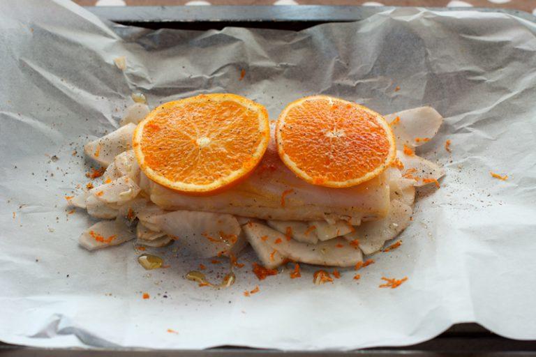 Stendete un foglio di carta forno e formate uno strato di topinambur su cui adagerete il filetto di merluzzo. Tagliate l'arancia restante e appoggiate un paio di fette per cartoccio.