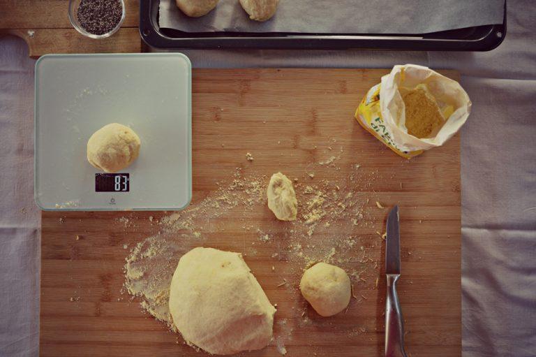 Spolverate la spianatoia con la farina di ceci; realizzate dei panini di circa 80 g l'uno, poneteli su una placca foderata con carta forno, effettuate dei tagli e pennellate con dell'acqua. Distribuite i semi di chia e una spolverata di farina di ceci.