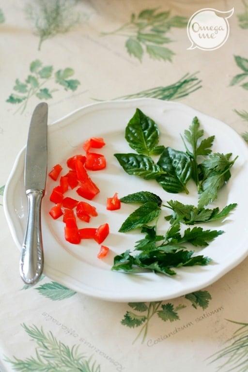 Spezzettare in un piatto i pomodorini e le erbe