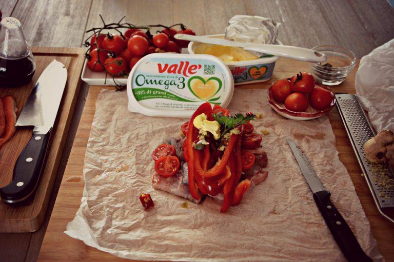 Unite dentro ogni cartoccio: 6 pomodorini tagliati a metà, un quarto di zenzero, un quarto dei capperi, un quarto dei filetti di peperone, qualche fogliolina di maggiorana, il peperoncino a rondelle, un po' di vino bianco, salate e chiudete il cartoccio.