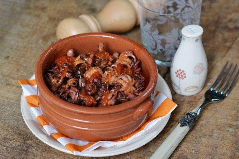 Servire i polipetti in tegami di coccio aggiungendo olive nere e pepe macinato.