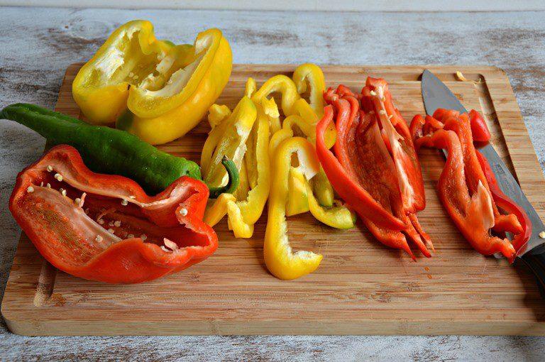 Lavate i peperoni, mondateli, eliminate i semi, tagliateli a strisce e saltateli in padella insieme con la cipolla tagliata a rondelle con un cucchiaio d'olio, coprite con un coperchio e portateli a un grado di cottura croccante circa 15 minuti. Salate a fine cottura