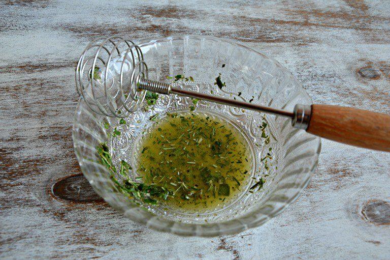 Emulsionate il succo del limone con l'olio e il trito di erbe aromatiche, salate leggermente e pepate