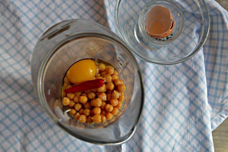 Mettete i ceci nel bicchiere del frullatore con le cipolle appassite, il prezzemolo, l'olio extravergine di oliva, il peperoncino, la farina e l'uovo.