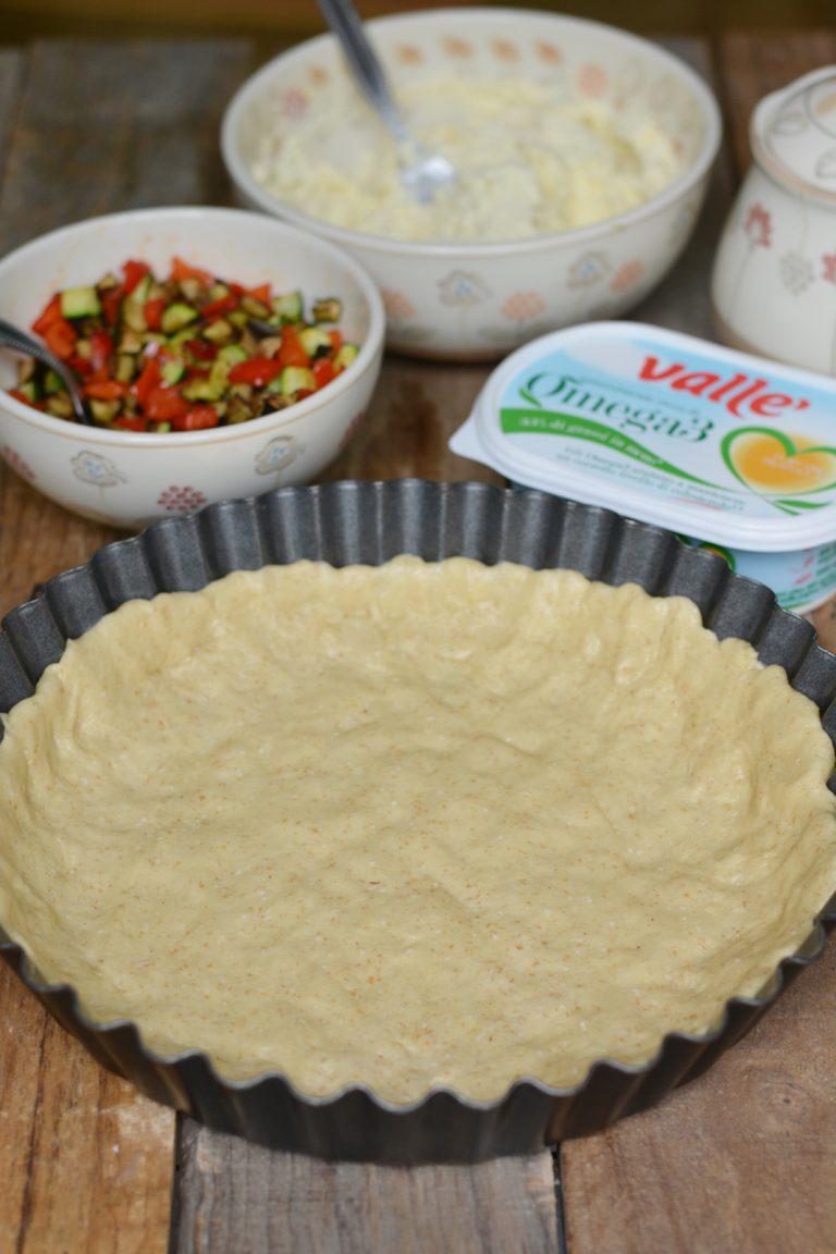 Preparare la frolla impastando tutti gli ingredienti: farine, acqua, Vallé e lievito. Stendere la frolla salata in uno stampo da crostata