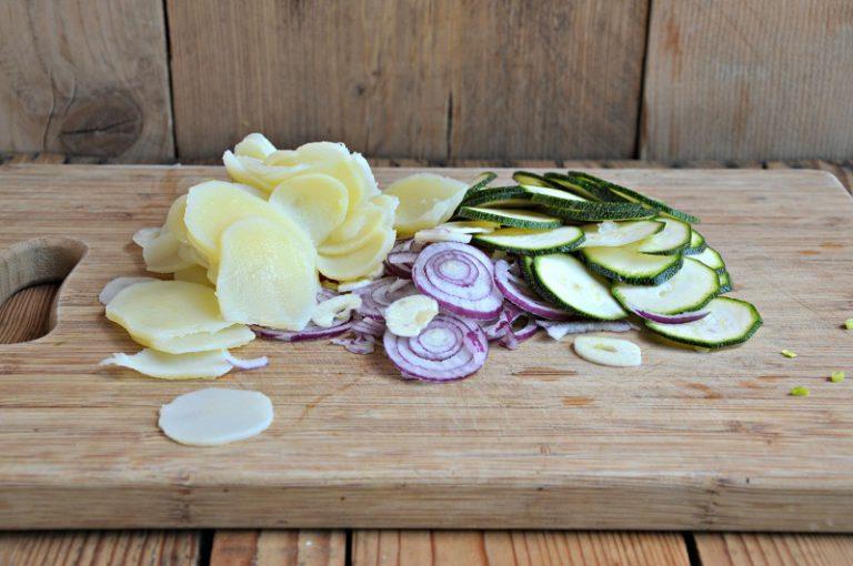 Affettate con una mandolina, le cipolle, l'aglio, le zucchine e le patate a rondelle sottili