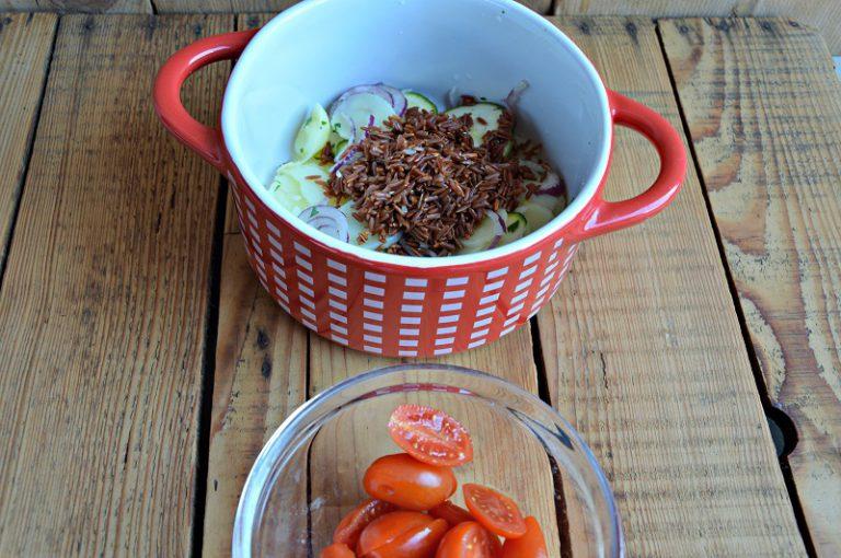 In una teglia da forno dai bordi alti mettete metà delle verdure affettate, il riso sciacquato e scolato e ben schiacciato, i pomodorini tagliati a metà.