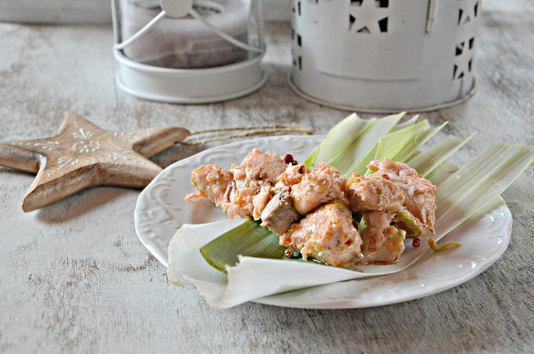 Con una pinza, prelevate i tocchetti di pesce e metteteli nel cestello della vaporiera. Nella pentola versate la marinata e dell'acqua bastevole per la cottura, due o tre dita. Portate a bollore l'acqua,ponete il cestello con il pesce e cuocete per 15 minuti. Servite su un letto di  foglie di porro.