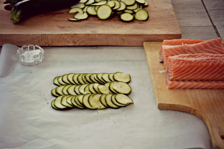 Preparate 4 cartocci con della carta forno, adagiate le rondelle di una zucchina e salate